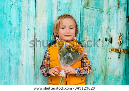 Autumn portrait of adorable little blond boy of 4 years old, wearing warm yellow vest coat, holding small bouquet of orange chrysanthemum flowers, standing in front of turquoise wooden wall - stock photo
