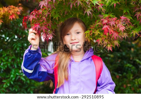Autumn portrait of adorable little girl wearing purple rain coat and red backpack - stock photo