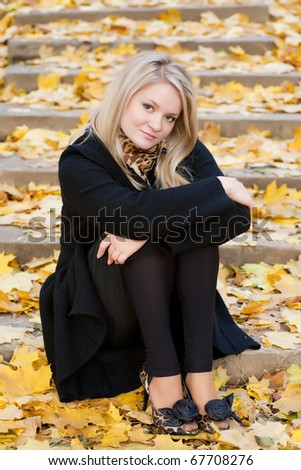 Autumn portrait of blonde girl on the stairs