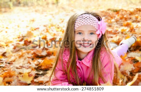 Autumn portrait of happy little girl with maple leaves outdoor - stock photo