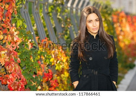 Autumn portrait of young woman in fall colors outdoors - stock photo