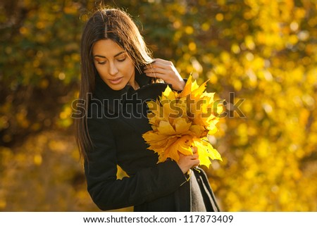 Autumn portrait of young woman in fall colors outdoors holding a bunch of yellow maple leaves - stock photo