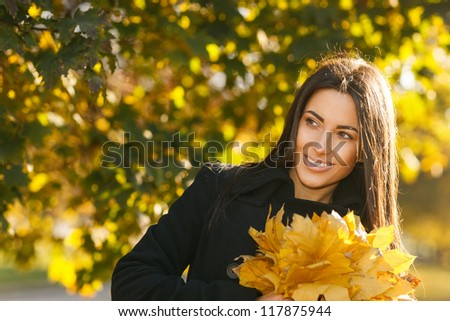 Autumn portrait of young woman in fall colors outdoors holding a bunch of yellow maple leaves looking to the side