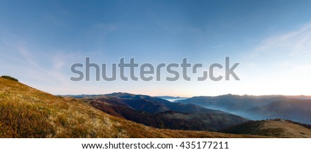Autumn predawn mountain panorama with clouds and last stars in sky.