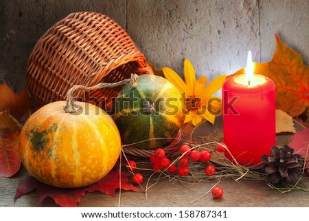 autumn pumpkin with a candle and a basket in the country house - stock photo