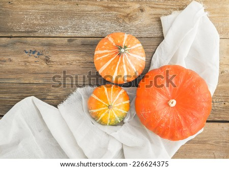 Autumn pumpkins on a piece of linen fabric over a wooden background - stock photo