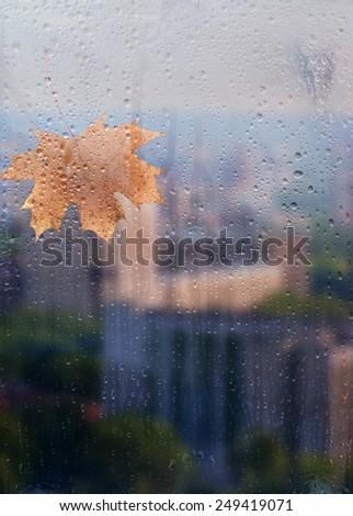Autumn, rainy city through a window with raindrops. autumnal mood. - stock photo