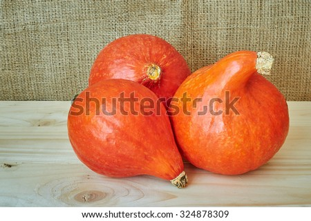 Autumn red pumpkins on a wooden background in a rustic style. Beautiful autumn Pumpkins Halloween background with place for text