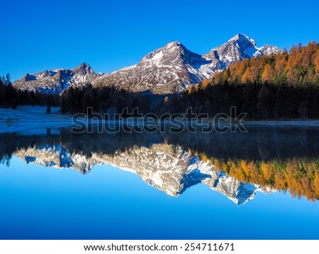 Autumn reflections on the lake Lej da Staz, Engadine Saint Moritz, Switzerland