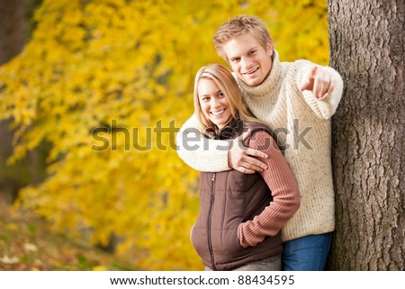 Autumn romantic couple happy together hugging in park tree pointing