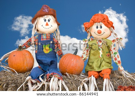 autumn scarecrow couple on hay bales - stock photo