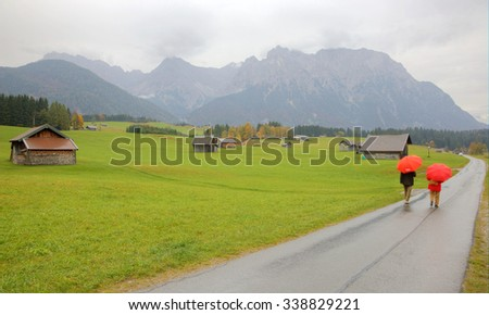 Autumn scenery of a ranch farmland near Mittenwald in a foggy drizzling morning ~ a road passing through a meadow with wooden barns and Karwendel mountains in the background in Bavaria, Germany - stock photo