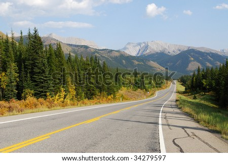 Autumn scenic view of rocky mountains and road (highway 40) while traveling in kananaskis country, alberta, canada - stock photo