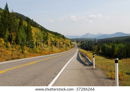 Autumn scenic view of rocky mountains, forests and road (highway 40) while traveling in kananaskis country, alberta, canada