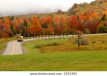 Autumn School Bus on Mountain Road - stock photo