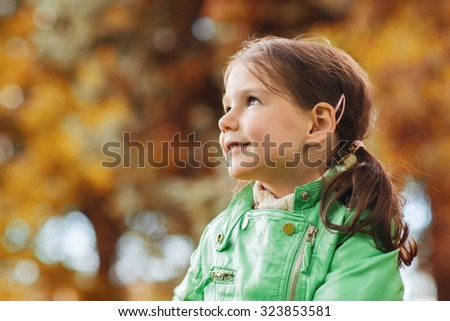 autumn, season, childhood, happiness and people concept - happy beautiful little girl portrait outdoors - stock photo