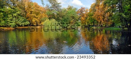 Autumn seasonal colors and reflections in Lazienki park in Warsaw. Panoramic wide view. - stock photo