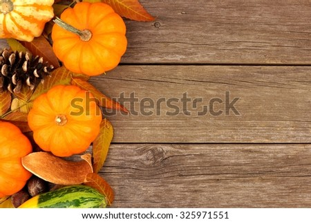 Autumn side border of pumpkins, leaves and gourds against a rustic wood background - stock photo