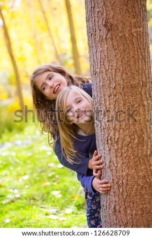 Autumn sister kid girls playing in poplar tree forest near trunk in nature outdoor - stock photo