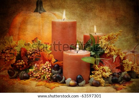 Autumn still life of burning candles surrounded by colorful leaves, pumpkins and acorns. - stock photo