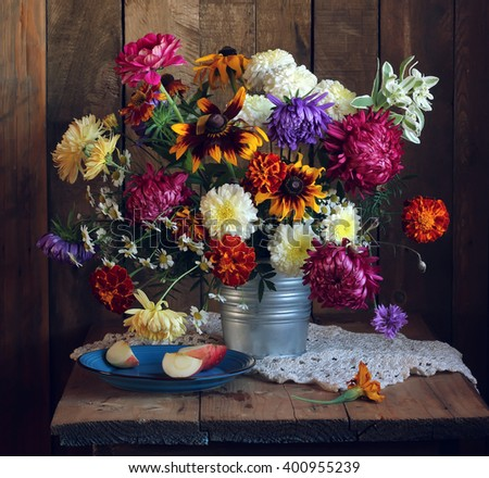Autumn still life with bouquet of flowers in a rustic style and slices of Apple on the blue plate on the background of boards. - stock photo