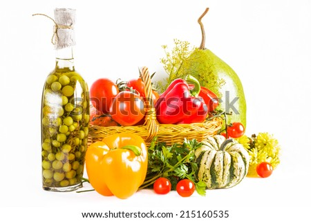 Autumn still life with different vegetables in wicker basket, pumpkin and bottle with marinated tomatoes - stock photo