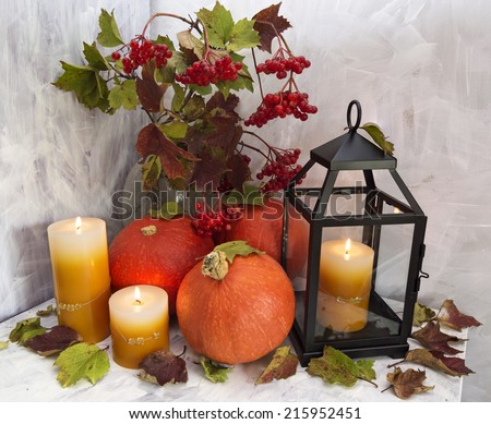 Autumn still life with pumpkins, lantern and candles on white - stock photo