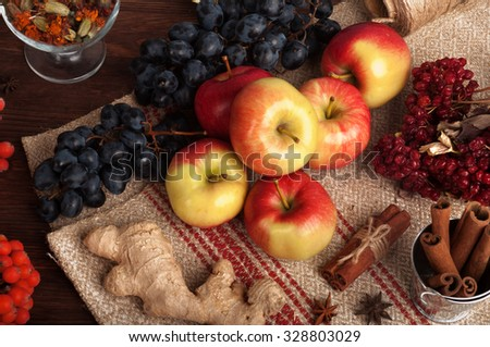 Autumn still life with red apples, grapes, cinnamon, star anise and ginger on a linen background; dried flowers in a glass; dark wood background, ingredients for cooking fresh pressed juice or cider