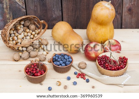 Autumn still life with walnuts and hazelnuts in the basket and autumn berry and vegetables on wooden background, closeup - stock photo