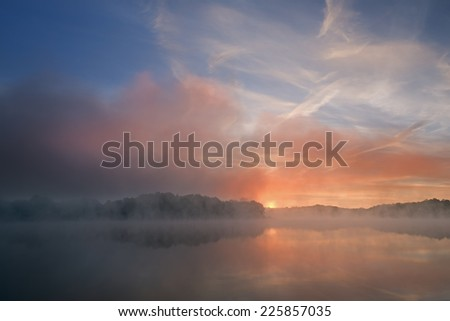 Autumn sunrise Whitford Lake in fog, Fort Custer State Park, Michigan, USA  - stock photo
