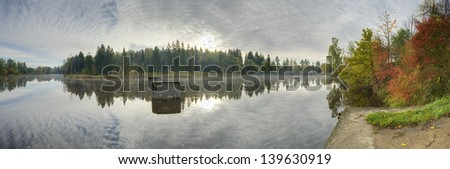 autumn sunrise with calm river on foreground