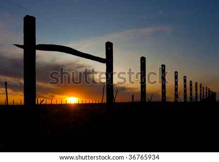 Autumn sunset with old fence