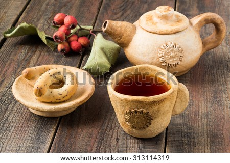 Autumn tea with hawthorn in the cup, earthenware teapot, dried hawthorn, bagels on a saucer on a wooden table. Selective focus - stock photo
