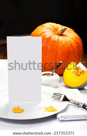 Autumn Thanksgiving dinner table setting with pumpkins and blank greeting card over wooden background.  - stock photo
