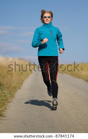 Autumn training - female running on the road - stock photo