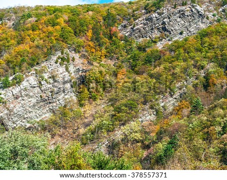 Autumn trees and exposed rock cliffs in the Delaware Water Gap Recreation Area between New Jersey and Pennsylvania.