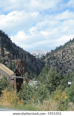 Autumn trees and pines with abandoned gold mine and mountain peak background - stock photo
