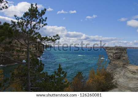 Autumn trees and rocky shoreline against deep blue water