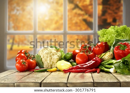 autumn vegetables on board and sun in window  - stock photo