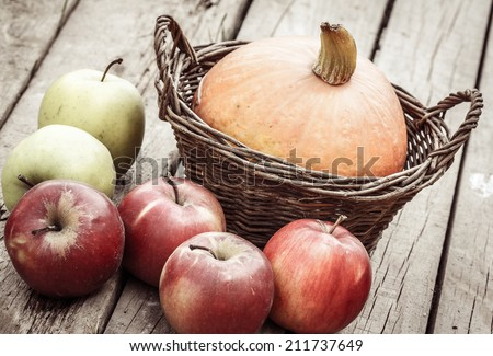 autumn vegetables - pumpkin in basket and apples - stock photo