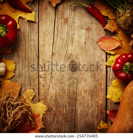 Autumn vegetables with autumn leaves on wooden background - stock photo