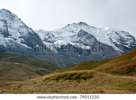autumn view from kleine scheidegg with pastures and snow covered mountain peaks, grindelwald range, swiss - stock photo