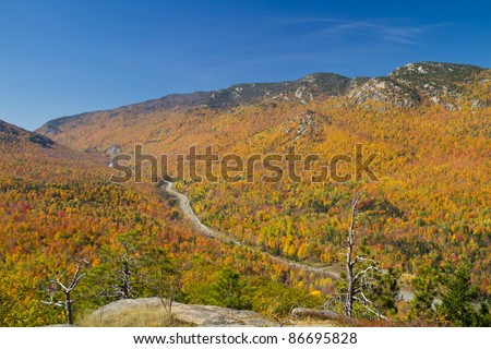 Autumn view from the top of Owl's Head mountain looking down on route 73  in Keene, NY - stock photo