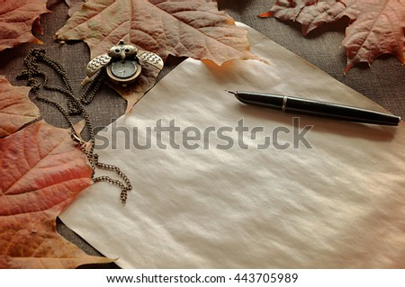 Autumn vintage view -old paper, ink pen on the table among the autumn leaves.Autumn vintage tones processing.Focus at the ink pen.Vintage autumn.Autumn concept, autumn objects, retro autumn still life - stock photo