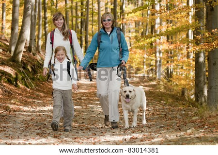 Autumn walking in forest - family with dog on trek