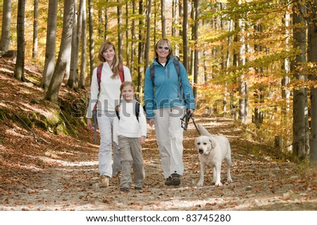 Autumn walking in forest - family with dog on trek - stock photo