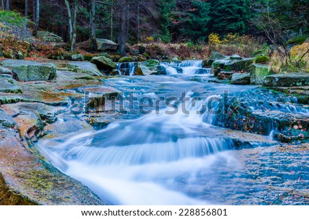 Autumn water cascades in a forest - stock photo