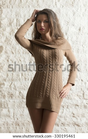autumn winter fashion shoot of sexy brunette woman with long hair, cute make-up and wool short dress. perfect sexy body