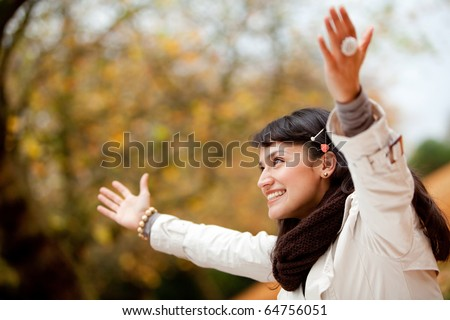 Autumn woman at the park with arms open - outdoors - stock photo