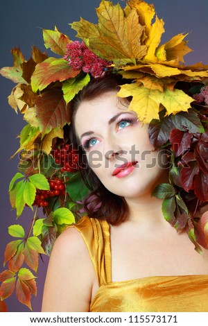 Autumn Woman. Beautiful makeup and hat from autumn yellow and red leaves and gold dress - stock photo